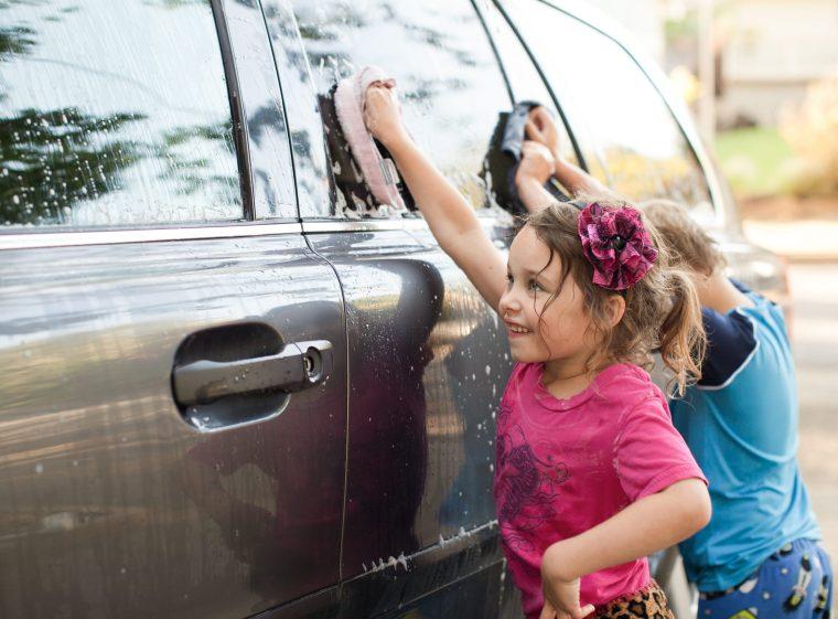Un garçon et une fille nettoient une voiture. La voiture est grise.
