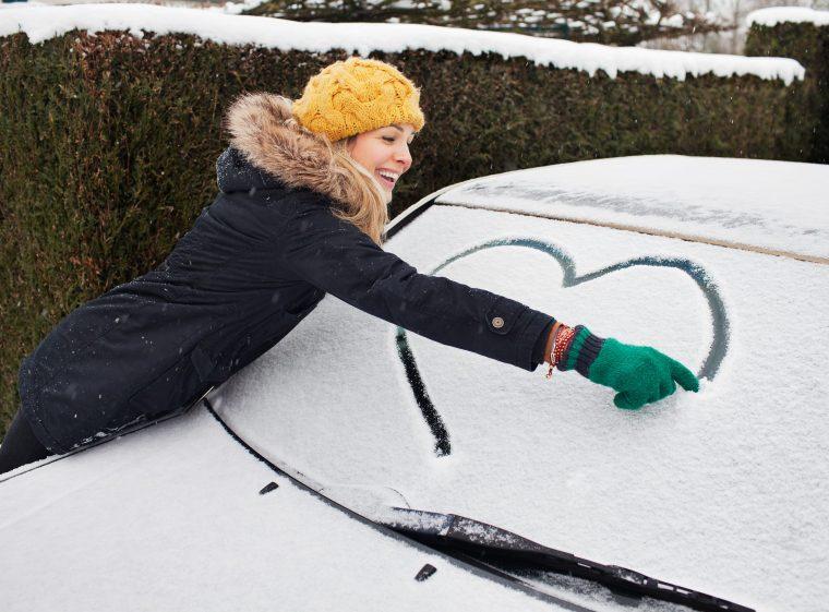 Une femme avec un bonnet et des gants dessine un cœur sur le pare-brise d'une voiture.