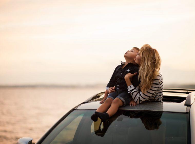 Un enfant est assis sur le toit d'une voiture. La mère tient l'enfant.