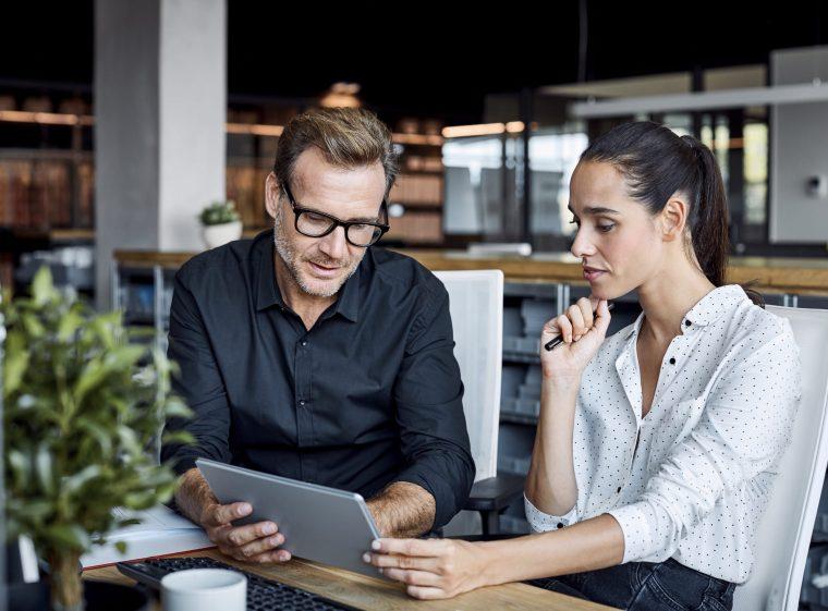Un uomo e una donna stanno avendo una conversazione. Insieme tengono in mano un tablet e stanno riflettendo su qualcosa.
