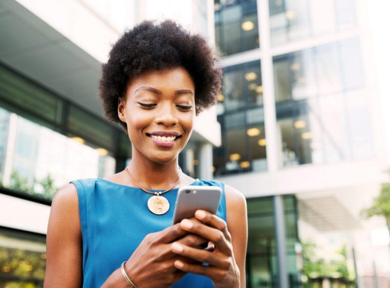 Une femme aux cheveux noirs et courts est devant un bâtiment. Elle écrit quelque chose sur un smartphone.
