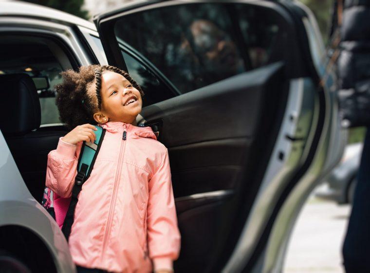 Une fille sort d'une voiture. La fille rit. Quelqu'un lui tient la porte.