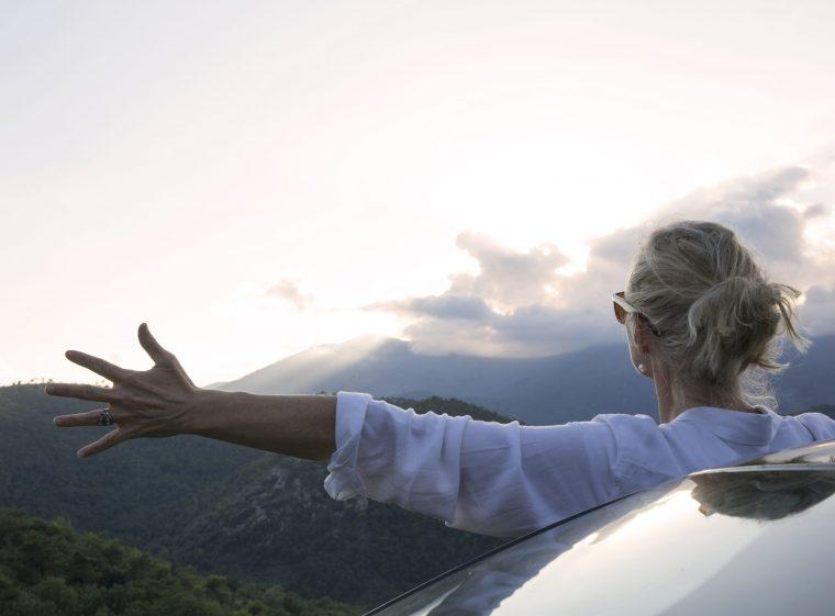Une femme est debout à côté de sa voiture, elle regarde le paysage.