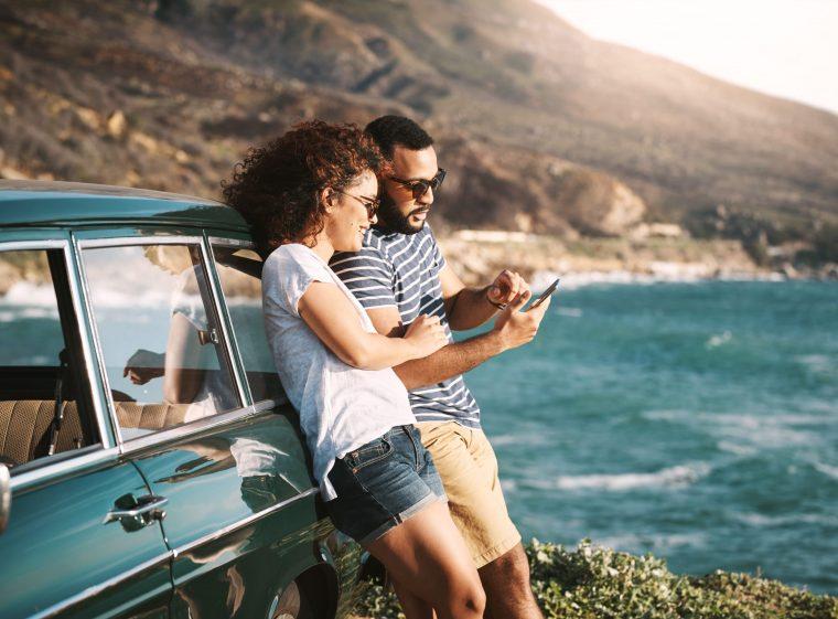 Una donna e un uomo sono appoggiati a un'auto verde. Entrambi indossano gli occhiali da sole.