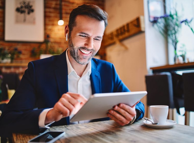 A man is sitting in a café. He is holding a tablet in his hand. He has headphones in his ears.