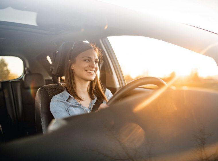 Une femme conduit une voiture. Le soleil se lève. La femme brune porte des lunettes de soleil.
