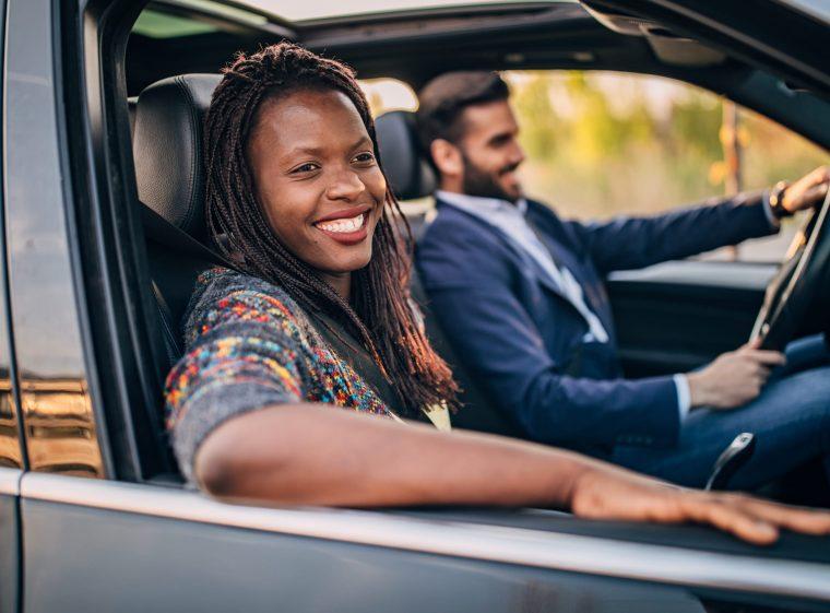Un homme en costume bleu conduit une voiture. La femme à côté de lui regarde par la fenêtre.