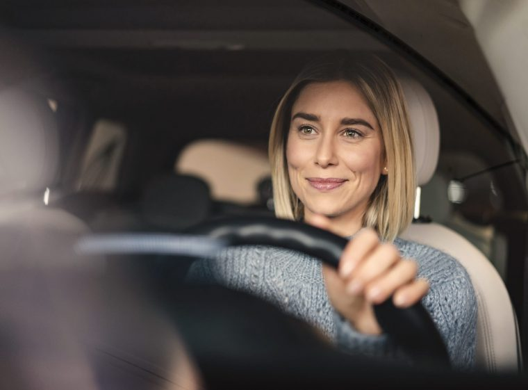 A woman is driving a car. The car has light-coloured seats. The woman has blond hair.
