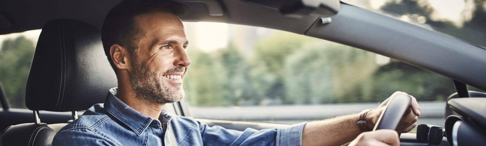A man smiling driving a car