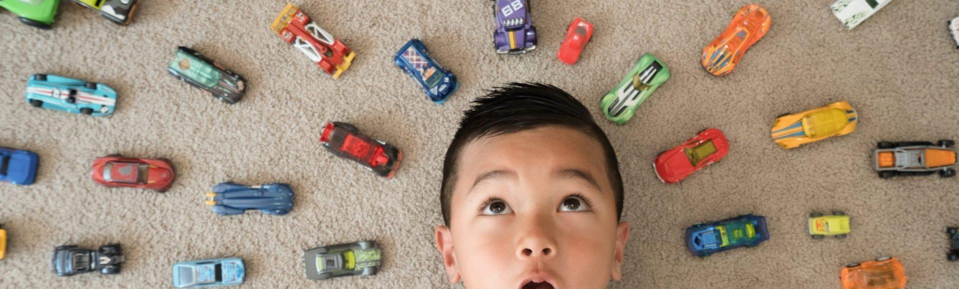 Intorno alla testa di un bambino ci sono tante auto giocattolo in fila