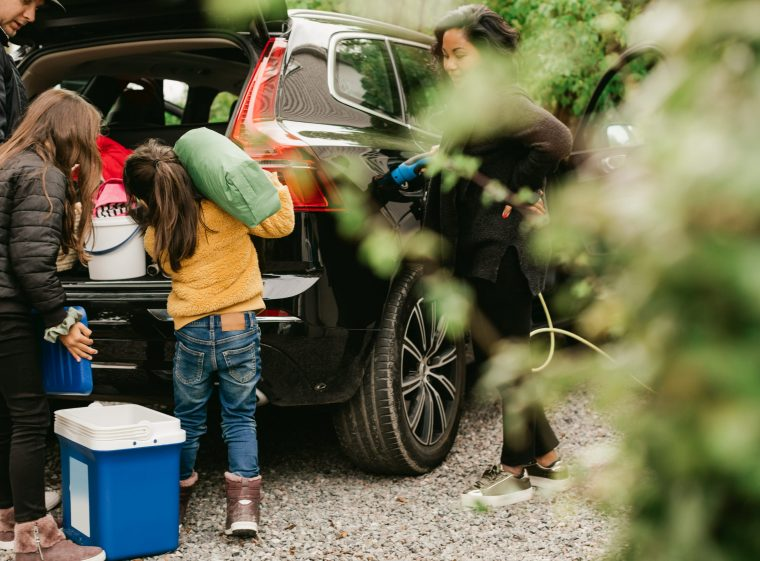 A family with two children is loading the car for a trip. The mother is loading the car.