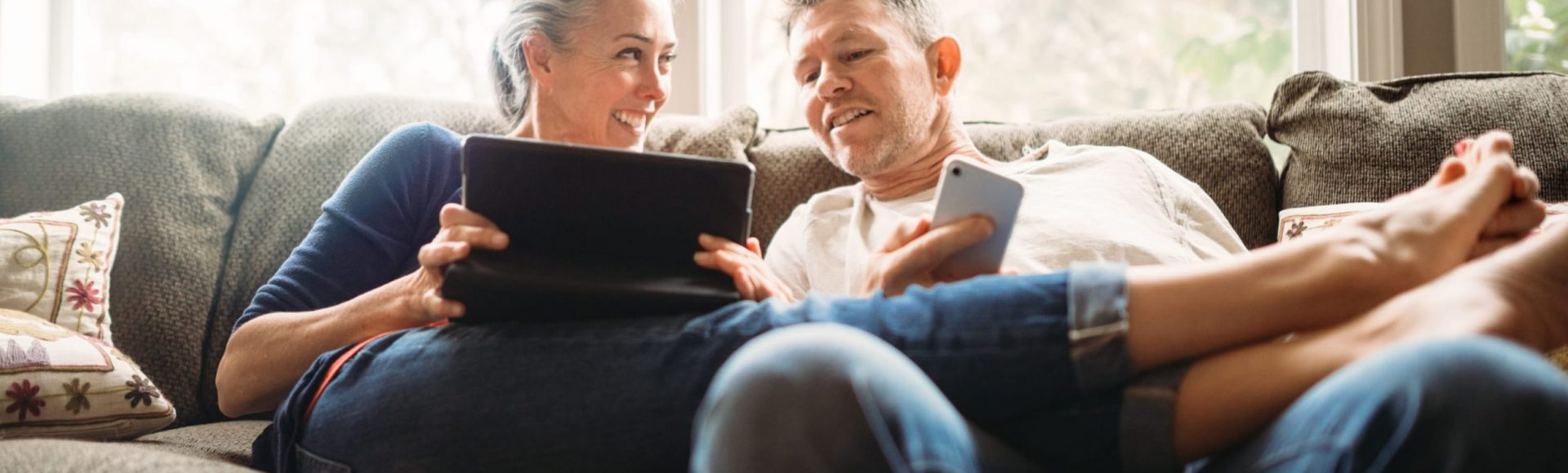 A man and woman are sitting on a sofa looking at a tablet