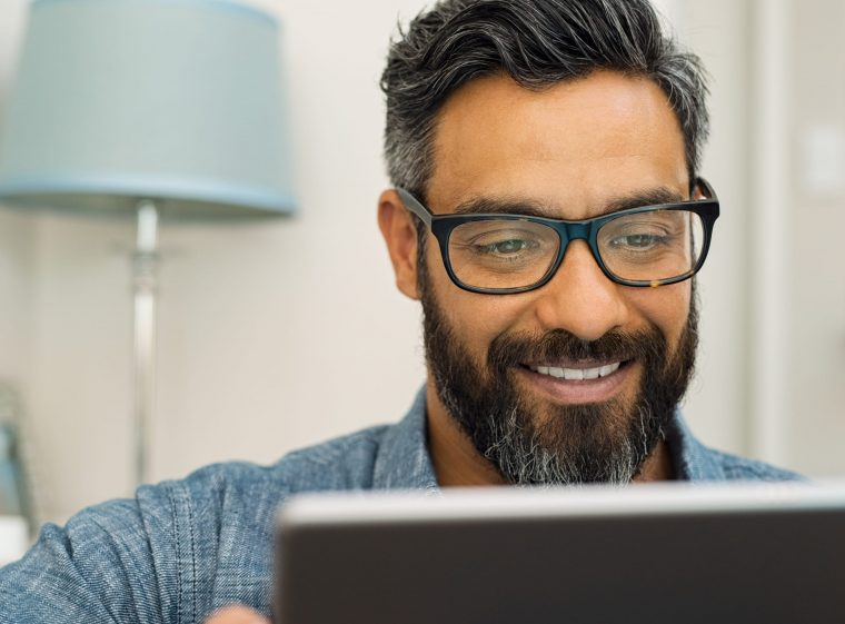 A man with black-grey hair and a beard is reading something on a tablet.
