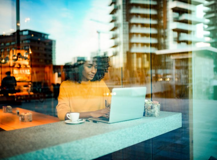 A woman is sitting in a restaurant. You can see her through the window. The woman has her laptop in front of her.