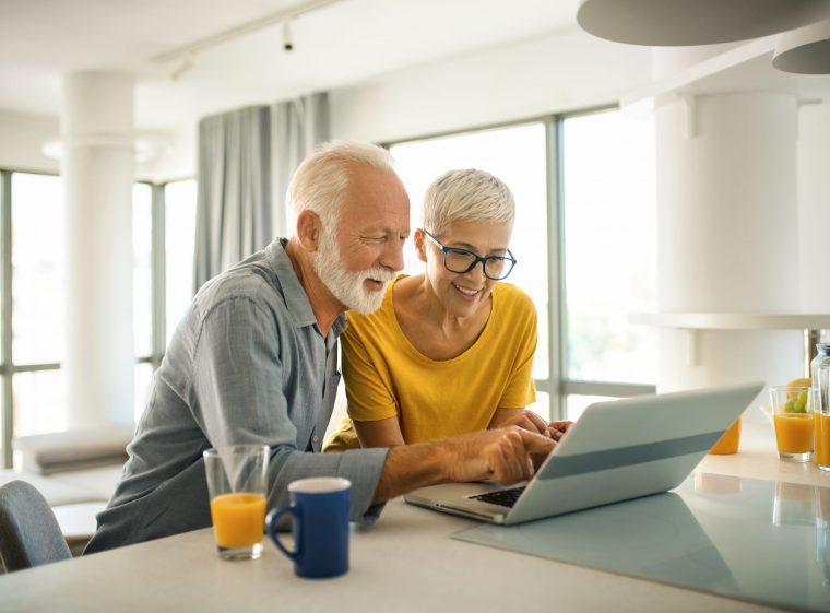 Un homme âgé et une femme plus jeune sont assis à table, devant un ordinateur.